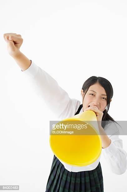 Female student shouting into megaphone, raising fist, studio shot