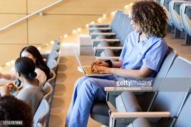 female student sitting alone in classroom takes notes on laptop - medical student stock pictures, royalty-free photos & images