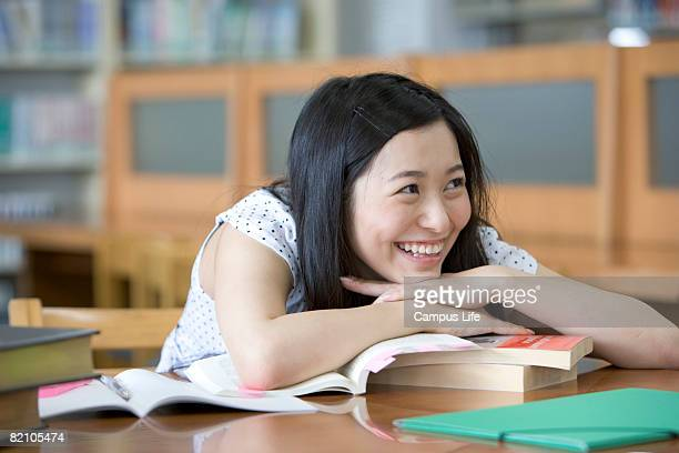 Female student sitting in library, smiling