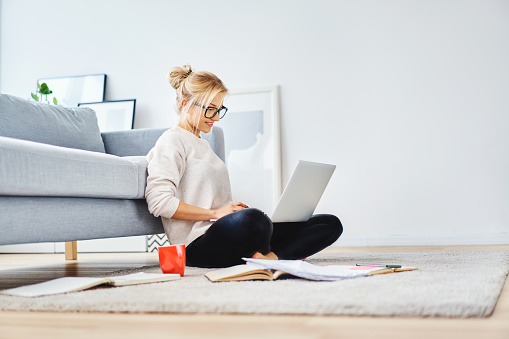 Female student sitting on floor of her apartment with laptop and notes studying 1098364450