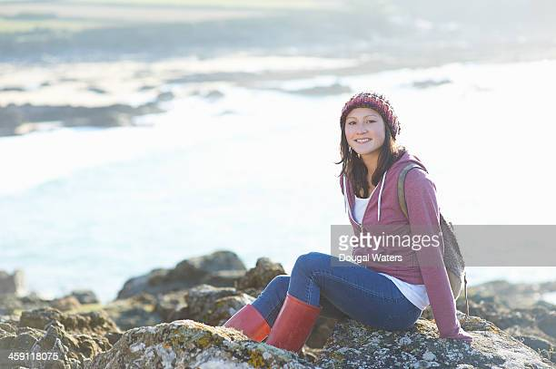female student sitting on rocks sea. - dougal waters stock pictures, royalty-free photos & images
