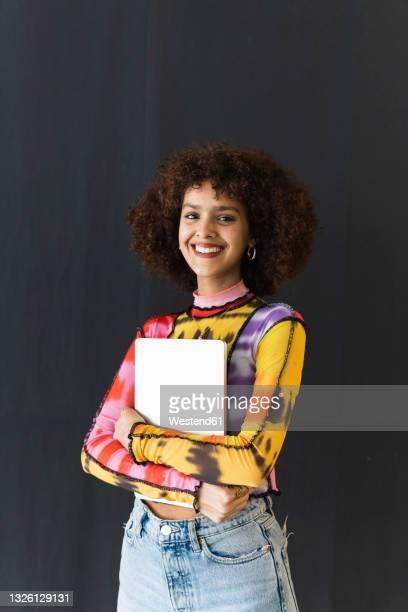 female student standing with book in front of black wall - three quarter length stock pictures, royalty-free photos & images