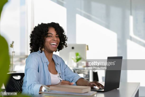 female student takes time from studying to smile for camera - mental wellbeing stock pictures, royalty-free photos & images
