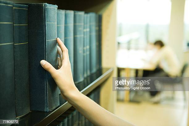 Female student taking reference book from shelf in library