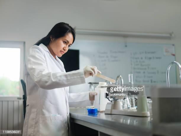 étudiant féminin utilisant l'échelle de nourriture dans le laboratoire - plan moyen angle de prise de vue photos et images de collection