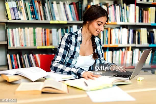 女子学生のラップトップを使用して研究のメモ