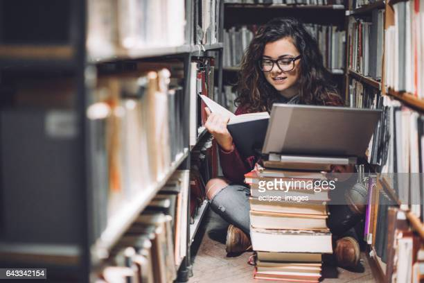 female student using laptop for taking notes to study - library stock photos and pictures