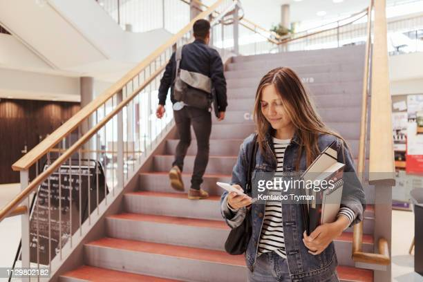 female student using mobile phone while man walking up on steps in university - campus stock pictures, royalty-free photos & images