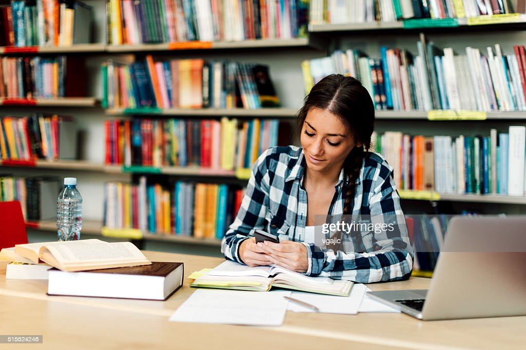 Female student using smart phone in library : Stock Photo