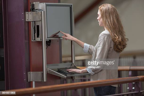 Female student using touch screen in a library