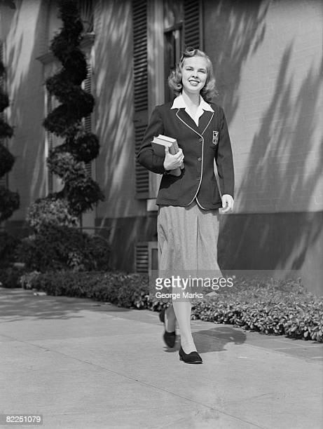 Female student walking outside school, portrait