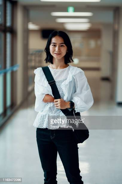 female student with an amputated arm in the hallway of a university campus - amputee woman stock pictures, royalty-free photos & images