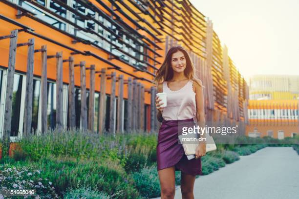 female student with coffee walking outside - mini skirt stock pictures, royalty-free photos & images