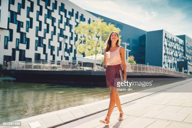 female student with coffee walking outside - business community stock pictures, royalty-free photos & images
