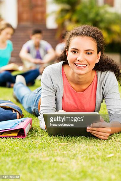 Female Student With Digital Tablet Lying On Campus