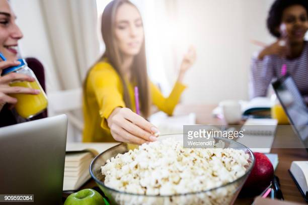 Female student with friends taking popcorn from bowl at table at home