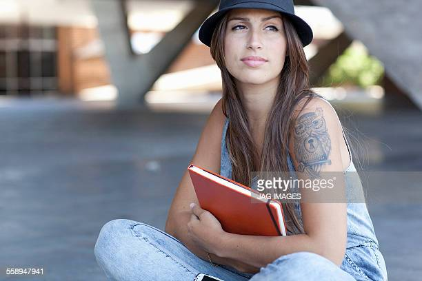Female student with tattoo holding book