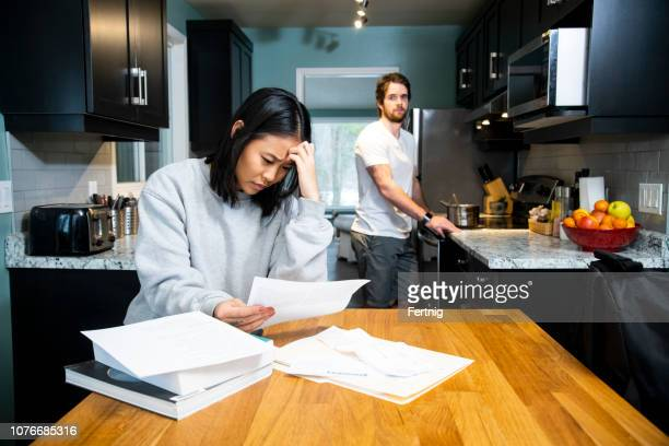 a female student worrying about financial issues at home in her apartment with her male friend cooking at the stove. - poverty stock pictures, royalty-free photos & images