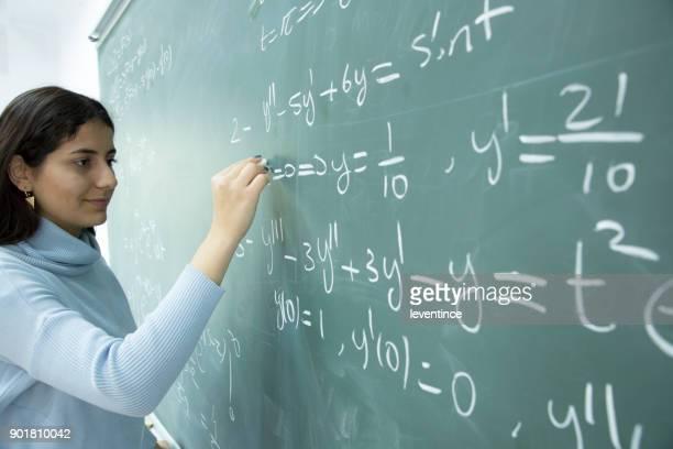 Studentin, die mathematische Formel vor der Tafel schreiben