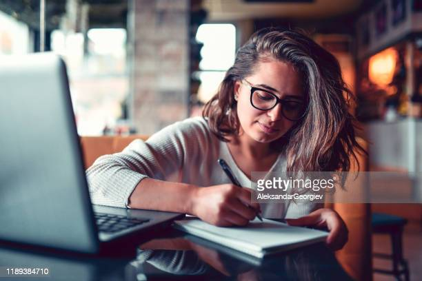 female student writing paper in coffee bar - author stock pictures, royalty-free photos & images