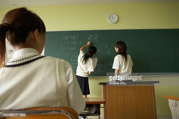 Female students (14-16) doing problem on blackboard, rear view