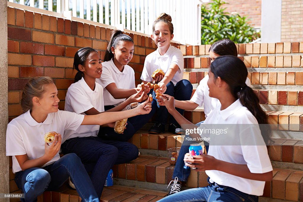 Female students having casual lunch at staircase : Stock Photo