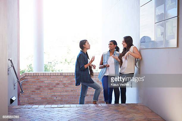 female students having discussion on staircase - trousers stock pictures, royalty-free photos & images