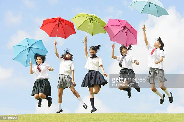 Female students holding colourful umbrellas jumping