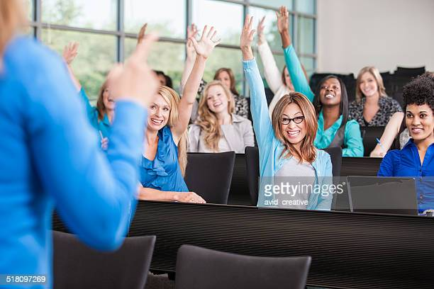Female Students in Classroom with Hands Raised