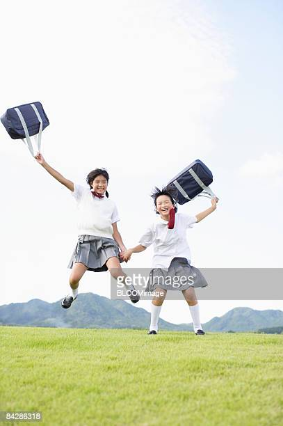 Female students jumping hand in hand, holding bags, smiling