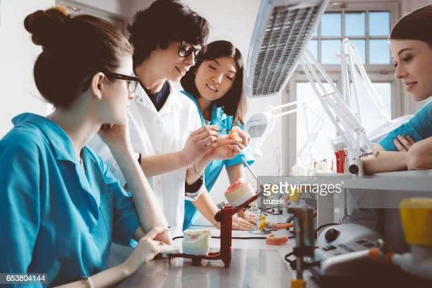 Female students learning prosthetic dentistry from teacher