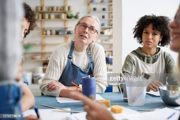 female students listening sitting at table in art class - craft stock pictures, royalty-free photos & images