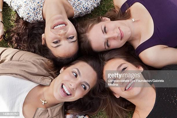 female students lying on grass, smiling - cuatro personas fotografías e imágenes de stock