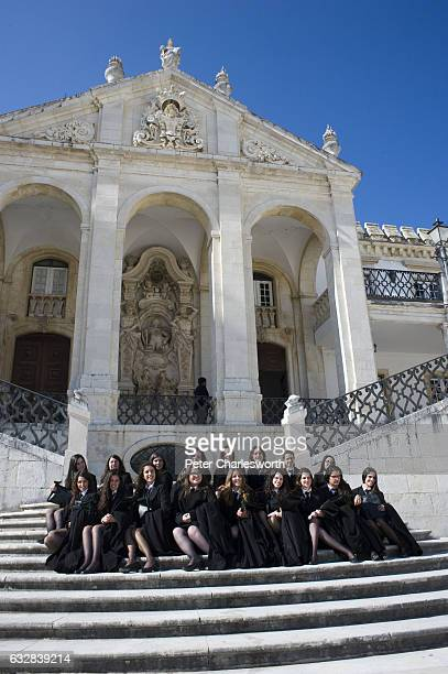 Female students of the Old University of Coimbra at a photoshoot practicing for their graduation ceremony in the Paco das Escolas square The public...