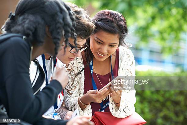 Female students on college campus reading smartphone texts