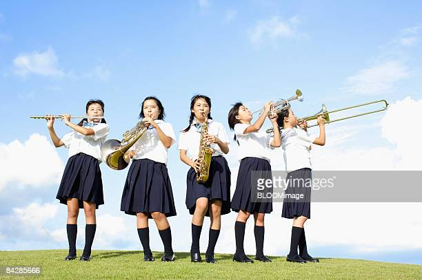 Female students playing musical instruments