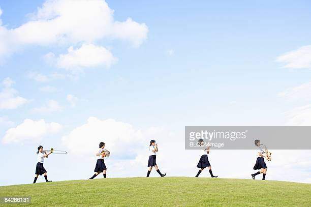 Female students playing musical instruments, walking in line