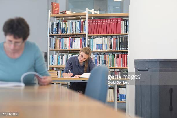 female students reading textbooks at library desks - sigrid gombert stock-fotos und bilder