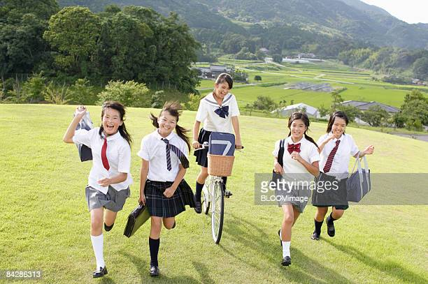 Female students running on grass and riding bicycle