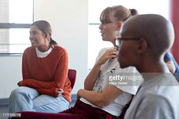 female students sitting in group therapy meeting - mental wellbeing stock pictures, royalty-free photos & images