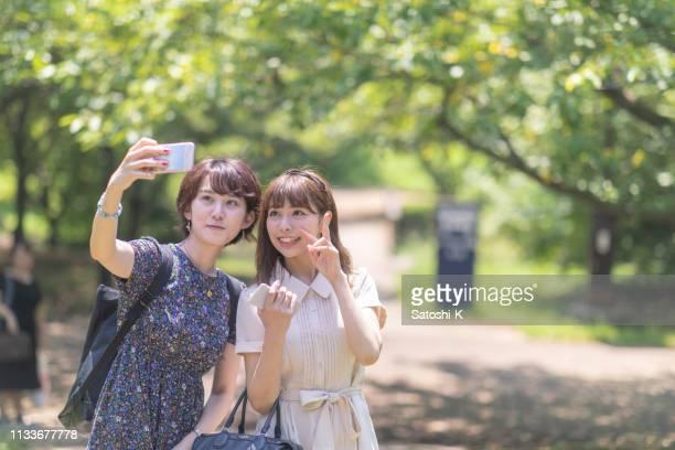 緑の森で自分撮り写真を撮る女子学生 - 女子大生 ストックフォトと画像
