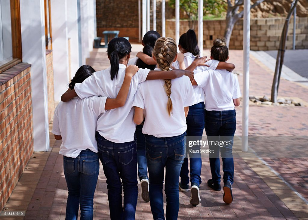 Female students walking together in schoolyard : Stock Photo