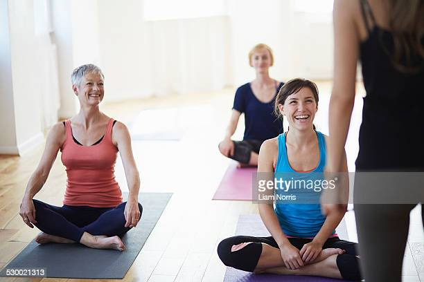 Female students watching and listening to tutor in pilates class
