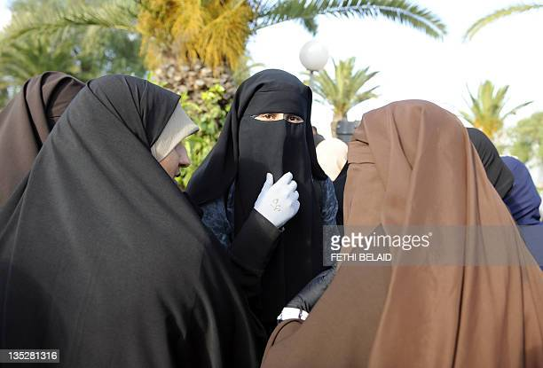 Female students, wearing a niqab, gather outside the building housing the office of the dean of the Faculty of Arts in Manuba, some 25 kms west of...