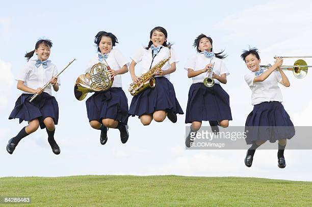 Female students with musical instruments jumping