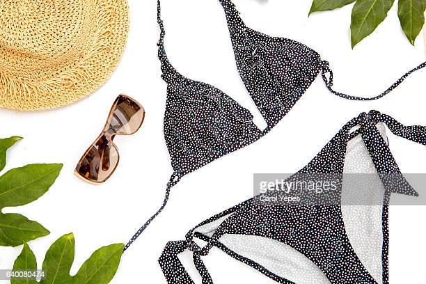 female summer bikini swimsuit accessories collage on white with hat, green branches, necklace and sunglasses. flat lay, top view