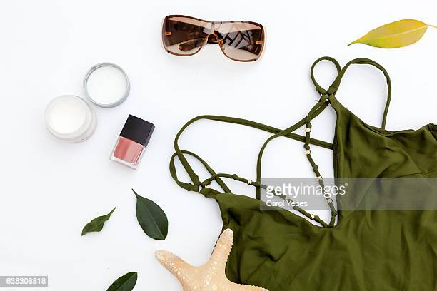 Female summer style bikini swimsuit and accessories collage on white with hat, green palm leaves, necklace and sunglasses. Flat lay, top view