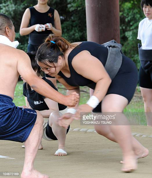 Female sumo wrestlers train with their coaches before competition of the Japan women's sumo championships in Sakai city southern Osaka on October 3...