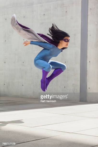 Female superhero levitating in mid-air against wall