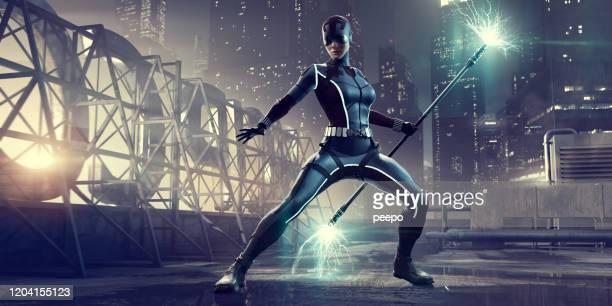 街の屋上に火花の武器を持って立っている女性スーパーヒーロー - スーパーヒーロー ストックフォトと画像